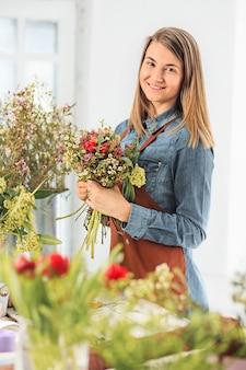 Fiorista che fa il mazzo di fiori diversi