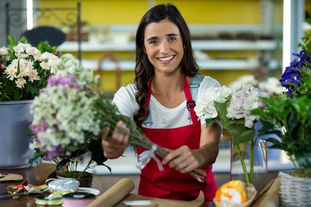 Fiorista che offre fiori al bancone del fioraio