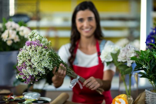 Fiorista che offre fiori al bancone