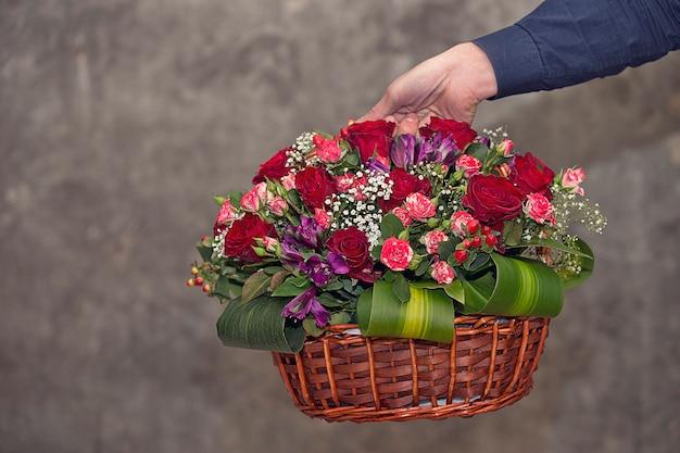 Fiorista che promuove un cesto di fiori misti.