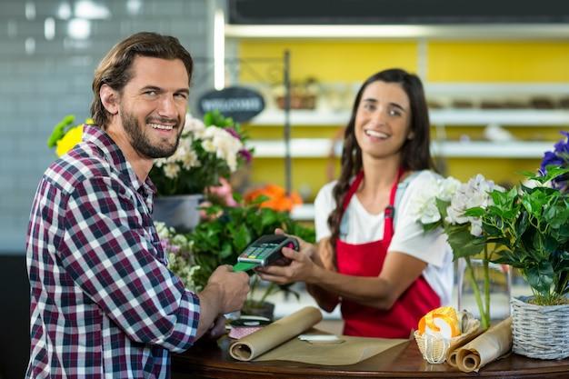 Fiorista che riceve un pagamento con carta di credito dal cliente nel negozio di fiori
