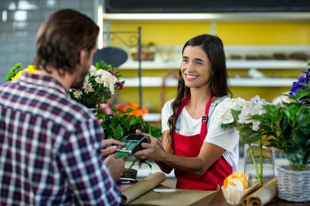 Fiorista che riceve un pagamento con carta di credito dal cliente