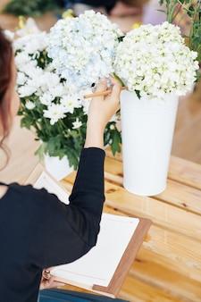 Fiorista che sceglie il tono dell'ortensia per la decorazione di nozze