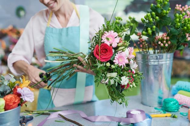 Fiorista che taglia steli di fiori