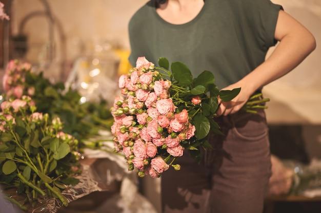 Fiorista che tiene il mazzo di fiori colorati in un negozio di fiori.