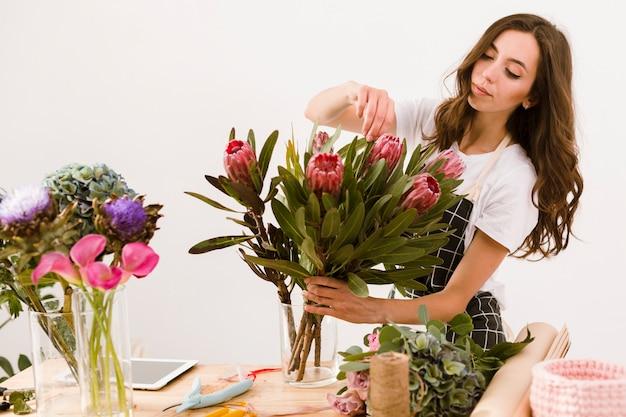 Fiorista del colpo medio che sistema il mazzo dei fiori