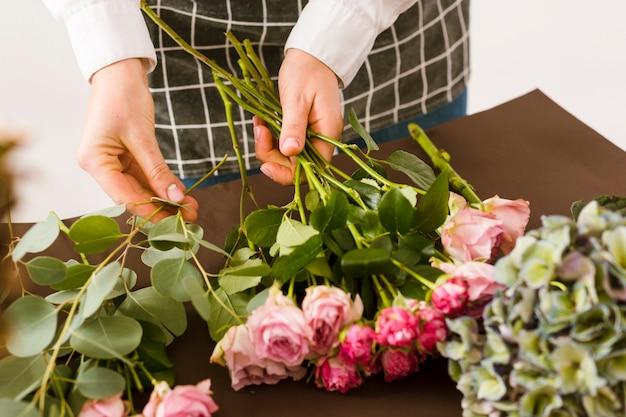 Fiorista del primo piano che sistema le rose rosa