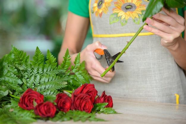 Fiorista della donna che prepara i fiori del mazzo.