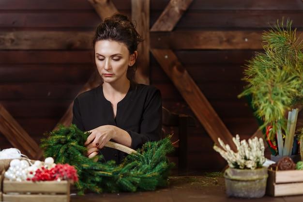 Fiorista di lavoro donna con ghirlanda di natale, giovane designer di donna sorridente carina preparare ghirlanda di alberi sempreverdi di natale.
