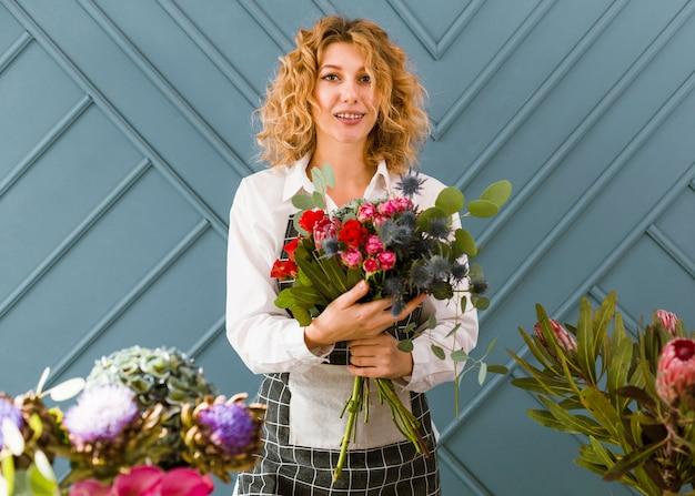 Fiorista di smiley del colpo medio che tiene un mazzo dei fiori