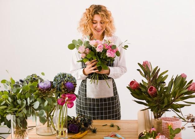 Fiorista felice del colpo medio che esamina i fiori