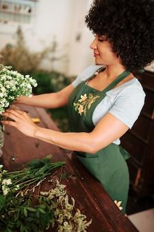 Fiorista femminile africano che sistema mazzo di fiori bianchi in vaso