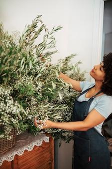 Fiorista femminile afro africano che esamina i fiori