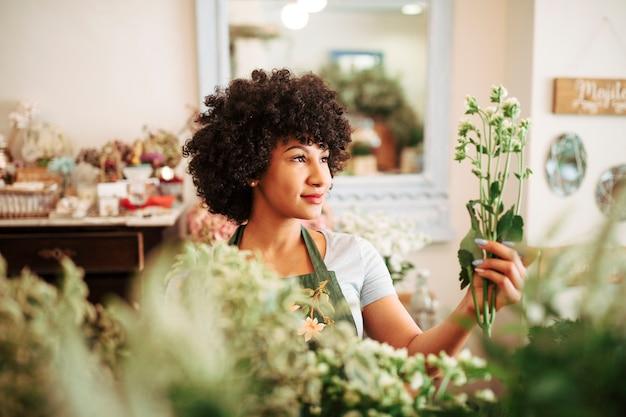Fiorista femminile afro africano che esamina mazzo di fiori bianchi