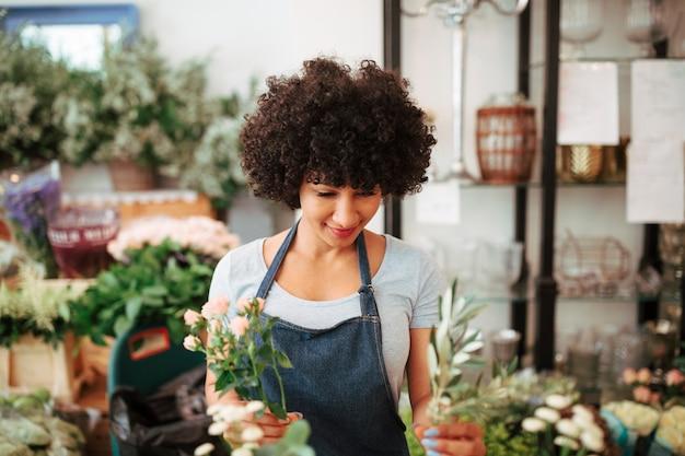 Fiorista femminile afro africano che sistema i fiori in negozio