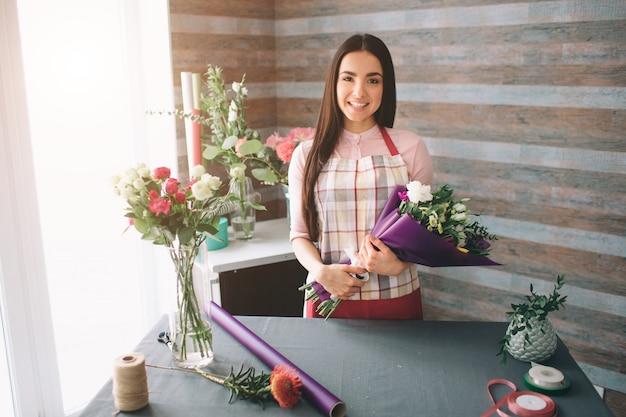 Fiorista femminile al lavoro: bella giovane donna dai capelli scuri che fa moda bouquet moderno di fiori diversi. donne che lavorano con i fiori in officina