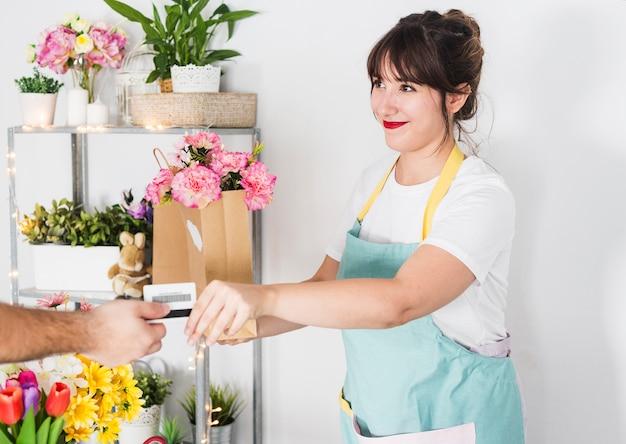 Fiorista femminile che dà il sacchetto di carta del fiore al suo cliente