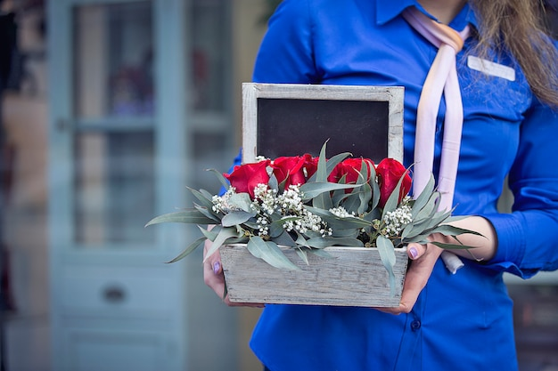 Fiorista femminile che promuove un cesto di fiori misti.