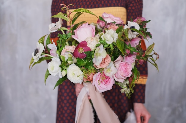 Fiorista femminile che tiene il mazzo floreale di fioritura appena fatto