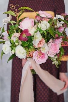 Fiorista femminile che tiene un mazzo floreale di fioritura appena fatto di pastello contro una parete grigia.
