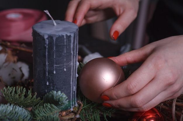 Fiorista femminile con palle di natale e candela nera