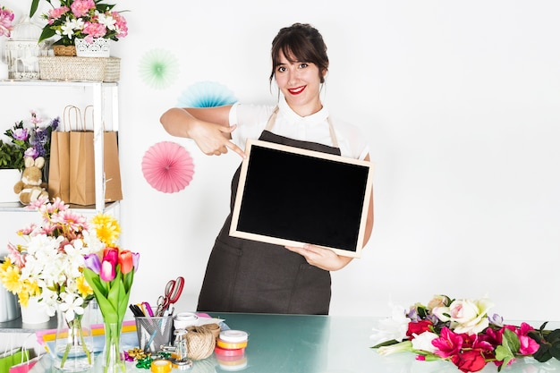 Fiorista femminile sorridente che indica all'ardesia in bianco nel negozio floreale