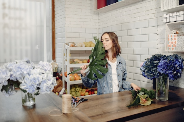 Fiorista in un negozio di fiori che fa un mazzo di fiori