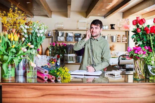 Fiorista maschio che accetta gli ordini sopra un telefono in un negozio di fiori