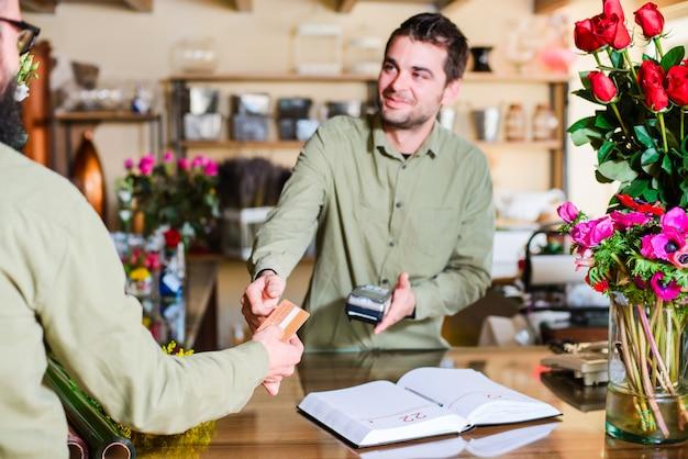 Fiorista maschio che fa pagare un cliente in un negozio di fiori