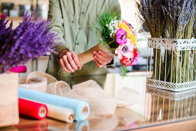 Fiorista maschio che mostra mazzo pronto in un negozio di fiore