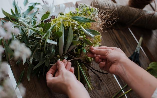 Fiorista professionista femminile prepara la composizione di fiori selvatici.
