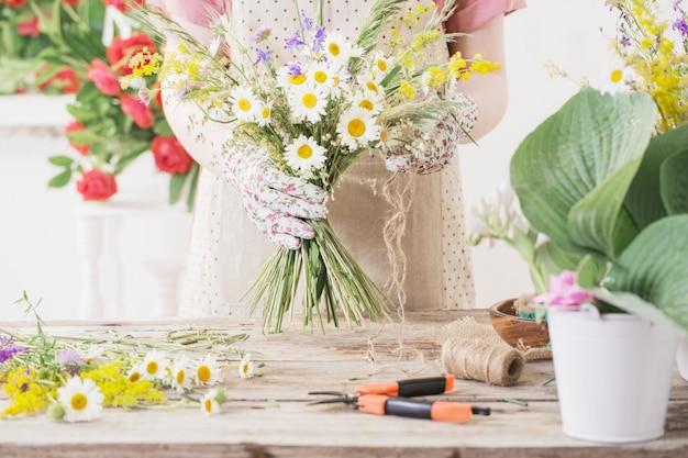 Fiorista ragazza fa bouquet di fiori di campo