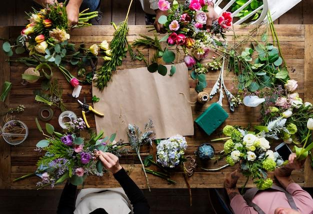 Fiorista rendendo la disposizione dei fiori freschi