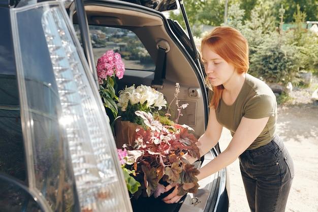 Fiorista rossa attraente serio in vestiti comodi che mette i fiori nel bagagliaio dell'auto mentre acquistano piante al mercato