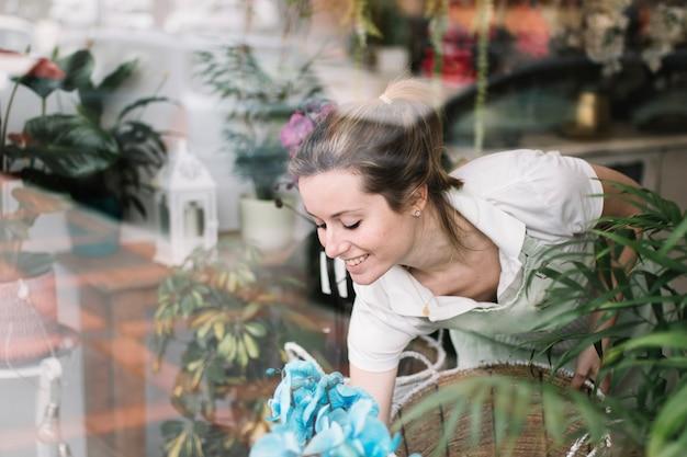 Fiorista sorridente che organizza la vetrina