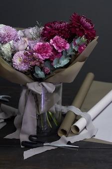 Fioristi desktop e viola tonica bouquet in stile vintage sul buio
