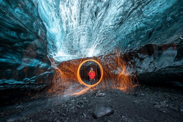 Fireshow della lana d'acciaio dentro una caverna di ghiaccio del ghiacciaio in islanda