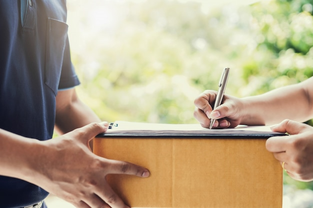 Firma della mano della donna su carta per la ricezione del pacco