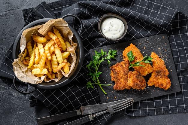 Fish and chips, patatine fritte e filetto di merluzzo fritto nel pangrattato. superficie nera. vista dall'alto