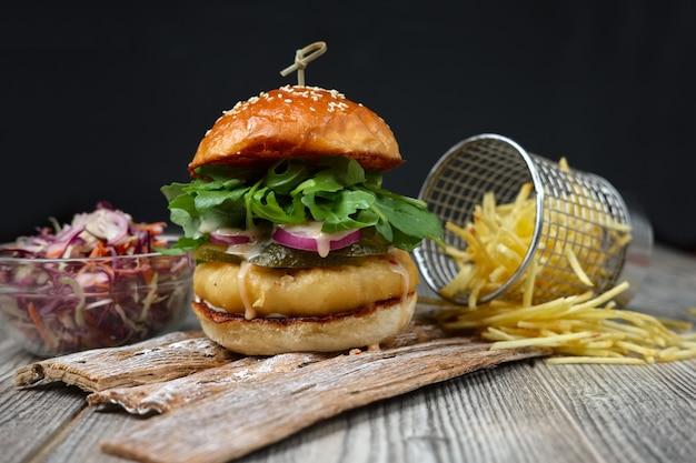 Fishburger sui piatti di legno con formaggio, cetriolo, cipolla, insalata verde e rossa e patatine fritte