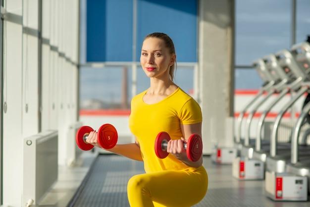 Fisicamente in forma bella donna in palestra che si esercita con manubri per rafforzare braccia e bicipiti