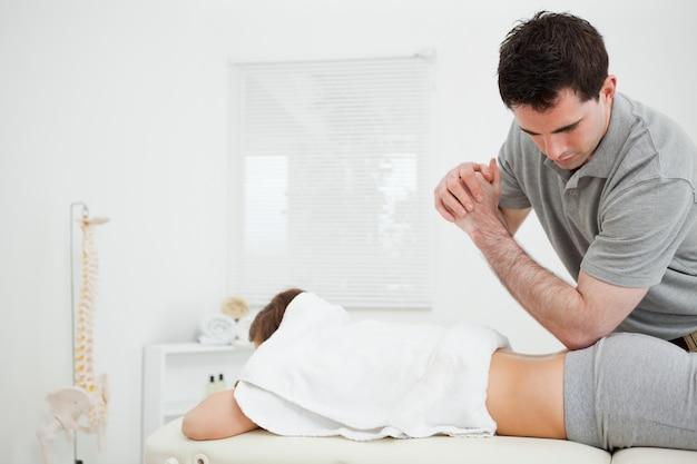 Fisioterapista castana che massaggia una donna con il suo gomito