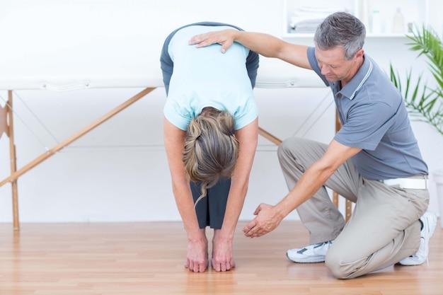 Fisioterapista che aiuta il suo paziente che allunga nell'ufficio medico