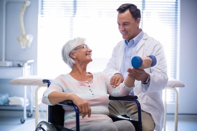 Fisioterapista che assiste il paziente senior con l'esercizio della mano