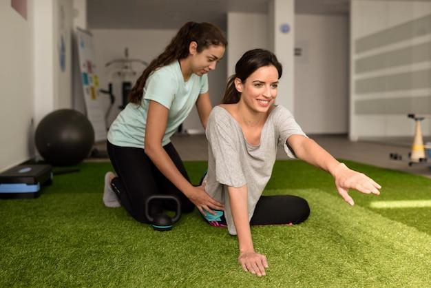 Fisioterapista che assiste la giovane donna caucasica con l'esercizio