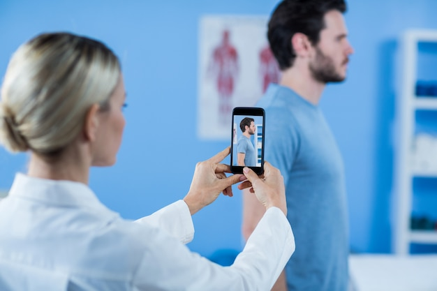 Fisioterapista che clicca foto di un paziente maschio