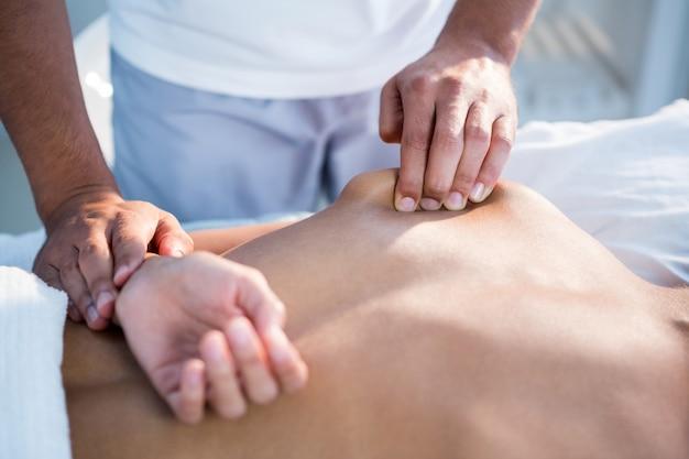Fisioterapista che dà massaggio alle mani a una donna