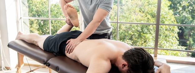 Fisioterapista che dà massaggio e che allunga paziente maschio in clinica