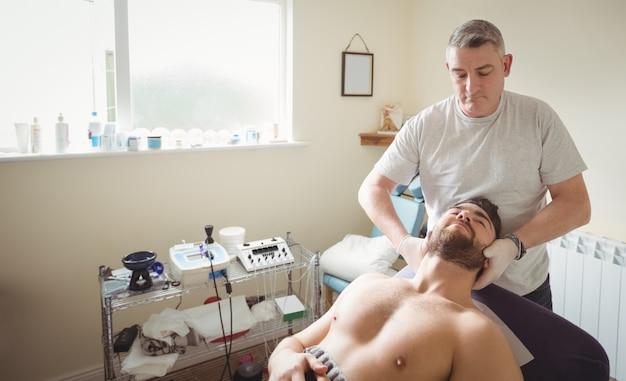 Fisioterapista che esamina collo di un paziente