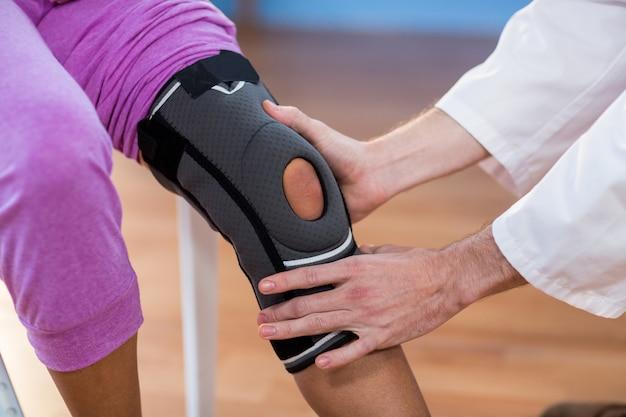Fisioterapista che esamina ginocchio femminile dei pazienti